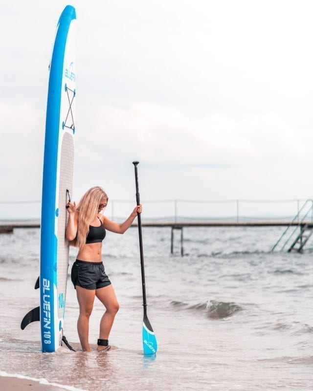 girl next to bluefin SUPs paddleboarding