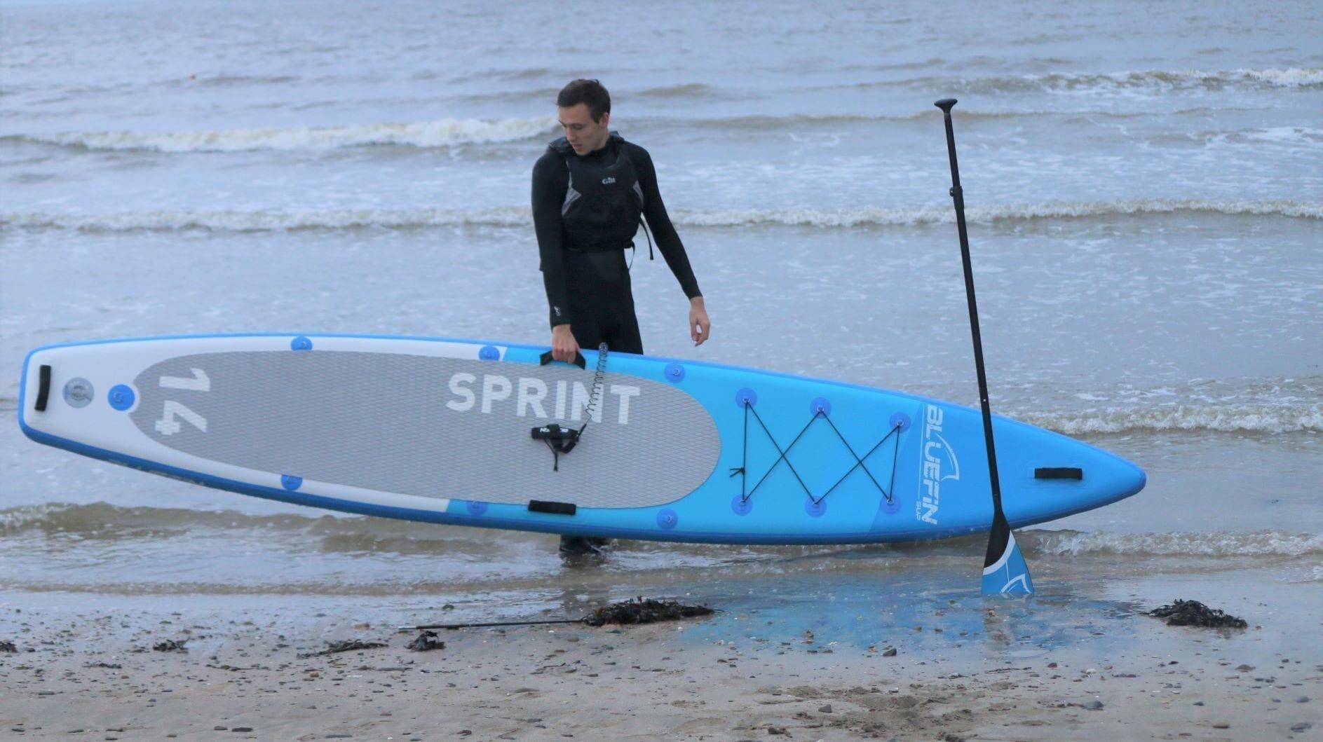 Harvey Merrin holds Bluefin Sprint SUP on the beach