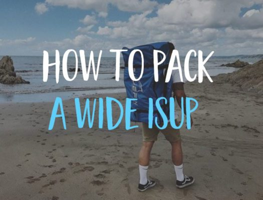 Man on beach in shorts carries iSUP in backpack