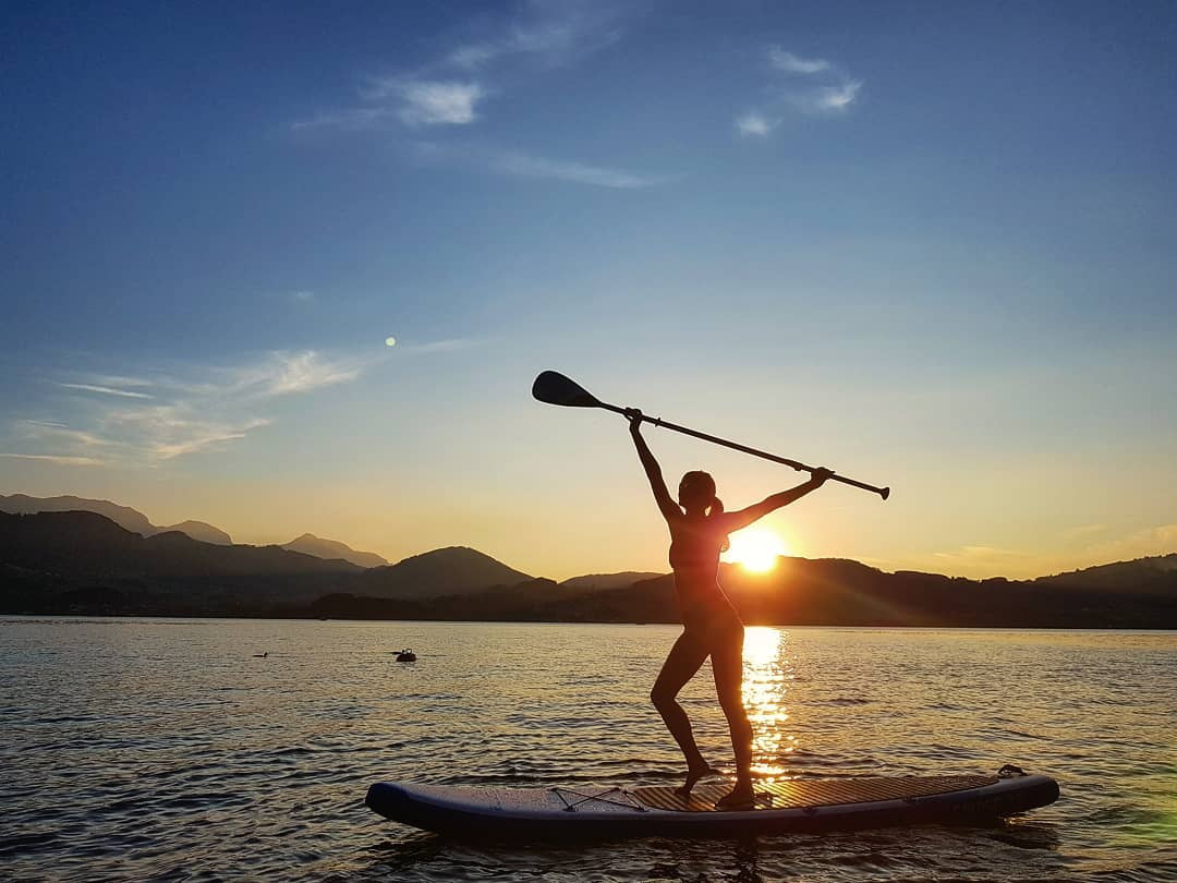 the sweet relief of safe keys lady in bikini stretching arms over head on paddleboard