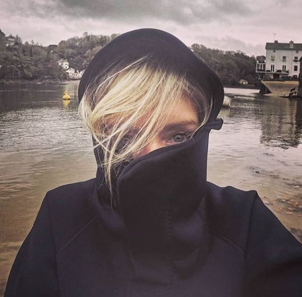blond lady in black hood standing on paddleboard